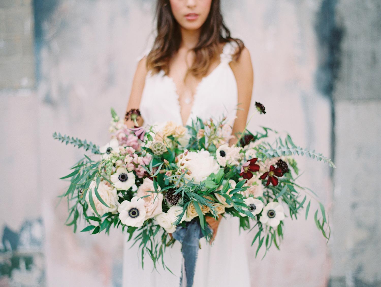 Bride holding a blue white green purple bouquet