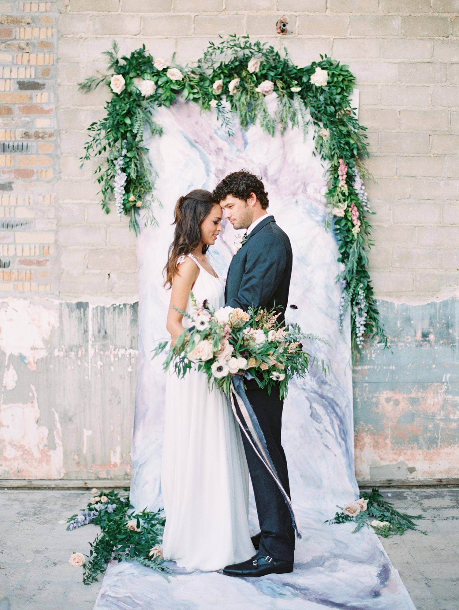 Bride and Groom in front of a moody marble backdrop