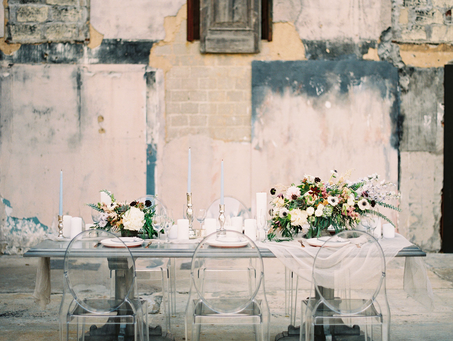 Grey farm table with a white runner and moody flowers