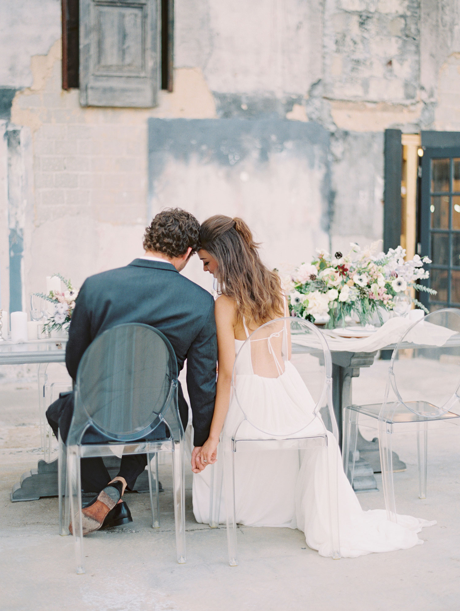Bride and groom sitting in ghost chairs at a reception