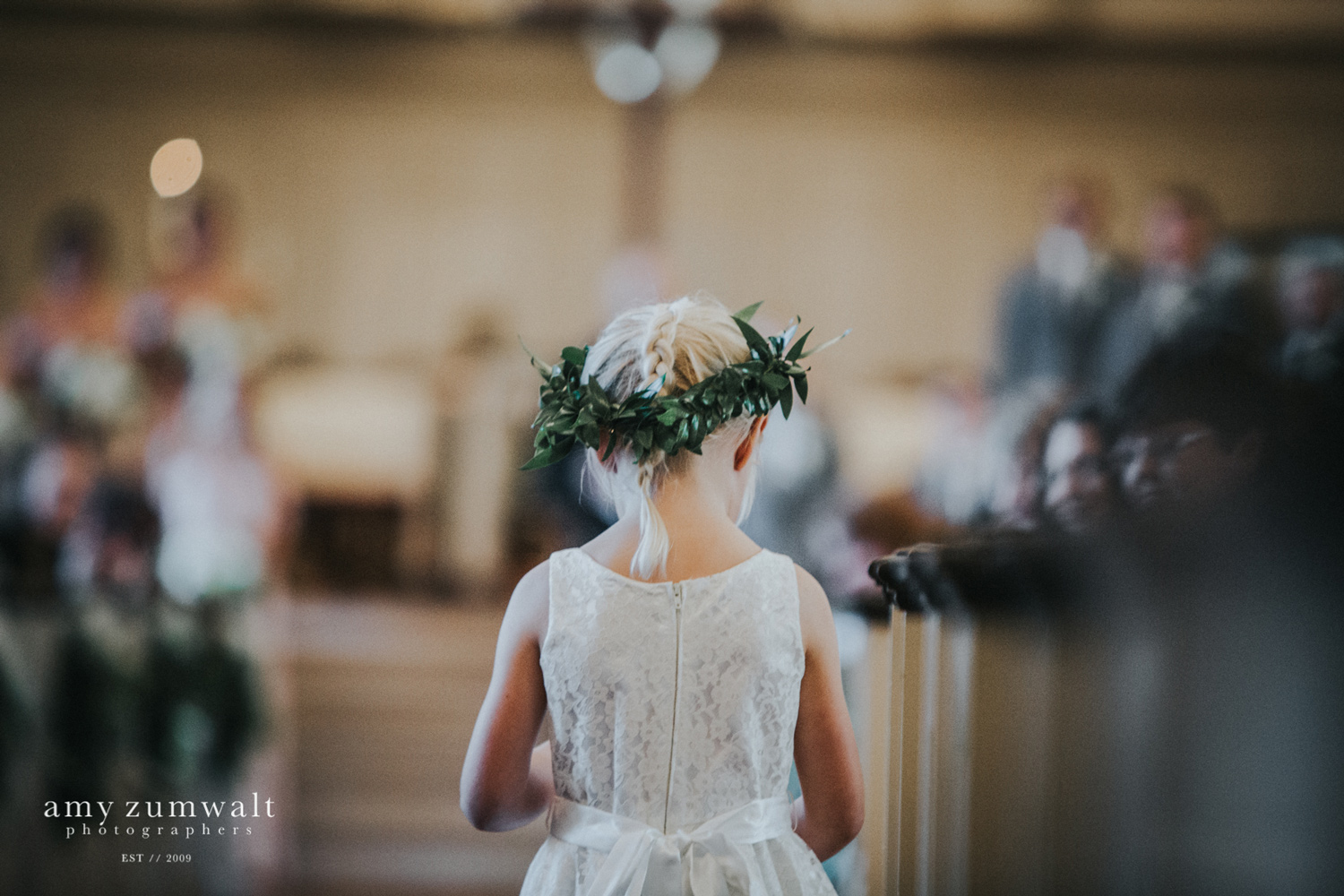 Flower girl with greenery floral crown walking down the aisle