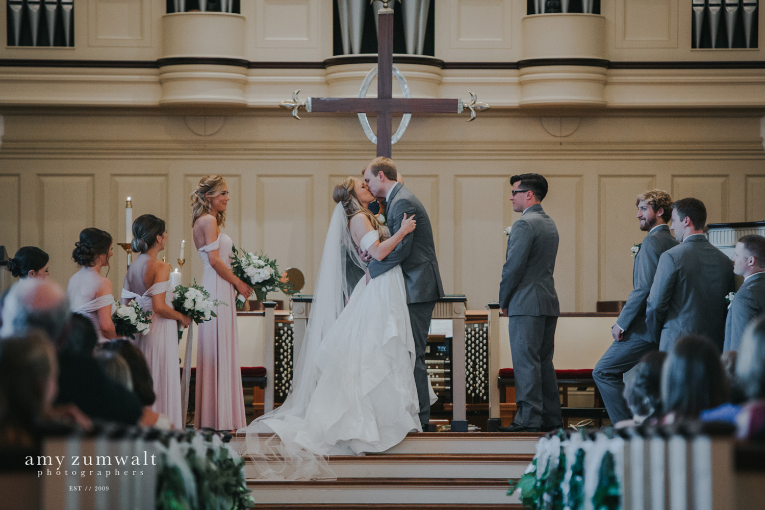Bride and groom first kiss in front of cross