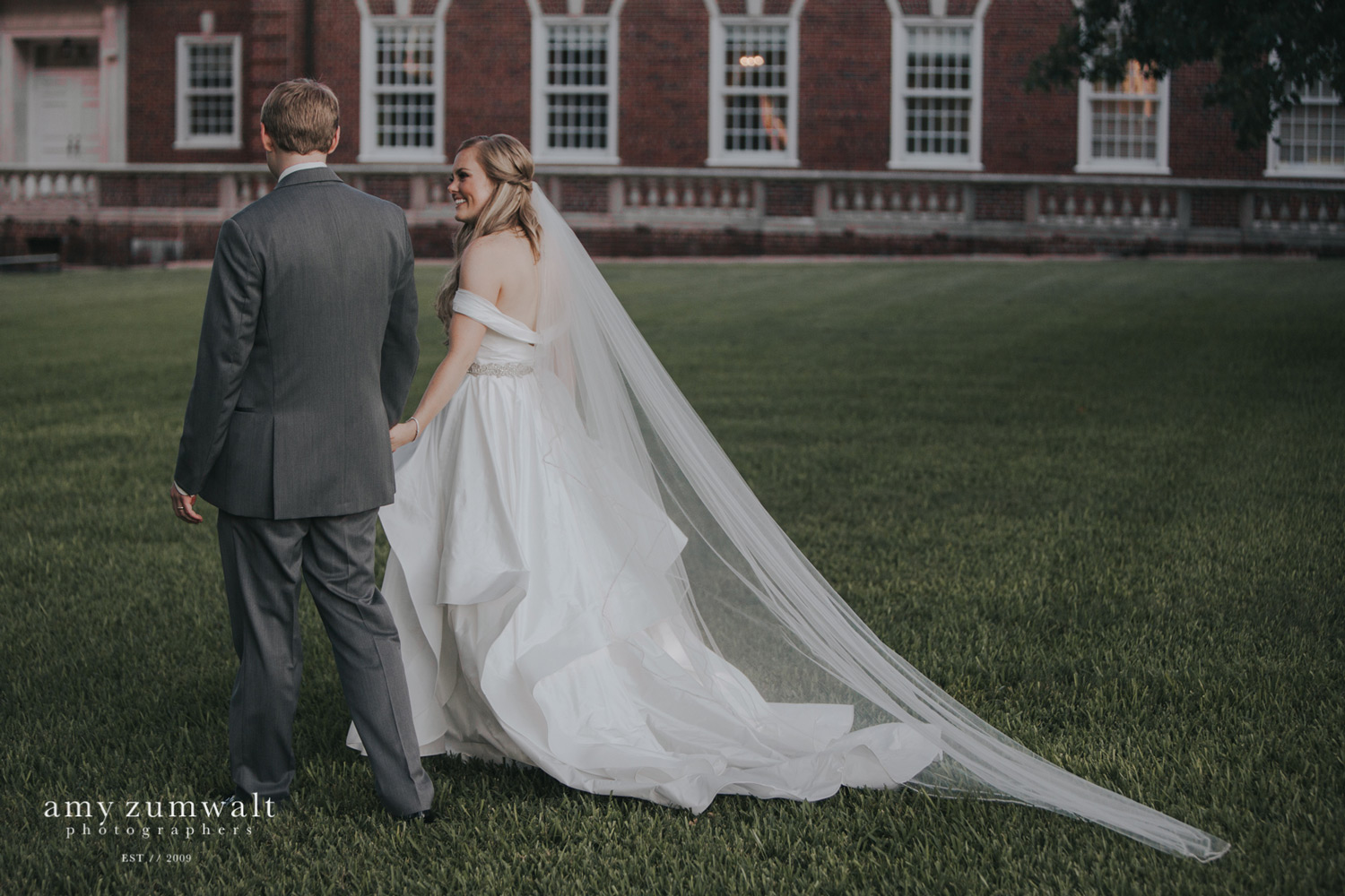 Bride and groom walking away in green field with cathedral veil