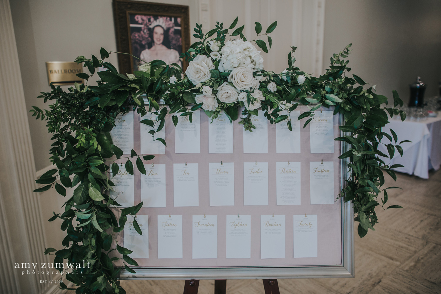 Gold frame seating chart with blush backing, gold frame, and white and green garland