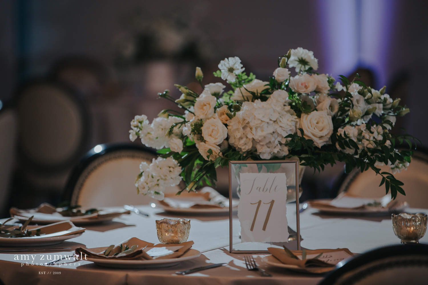 White and green flowers in a gold vase with a float frame table number