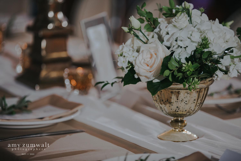 Small flower arrangment in gold urn on white chiffon runner