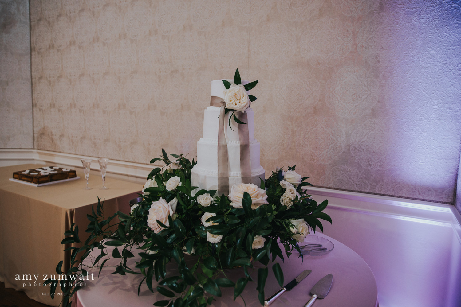 White wedding cake with taupe ribbon and greenery cake stand