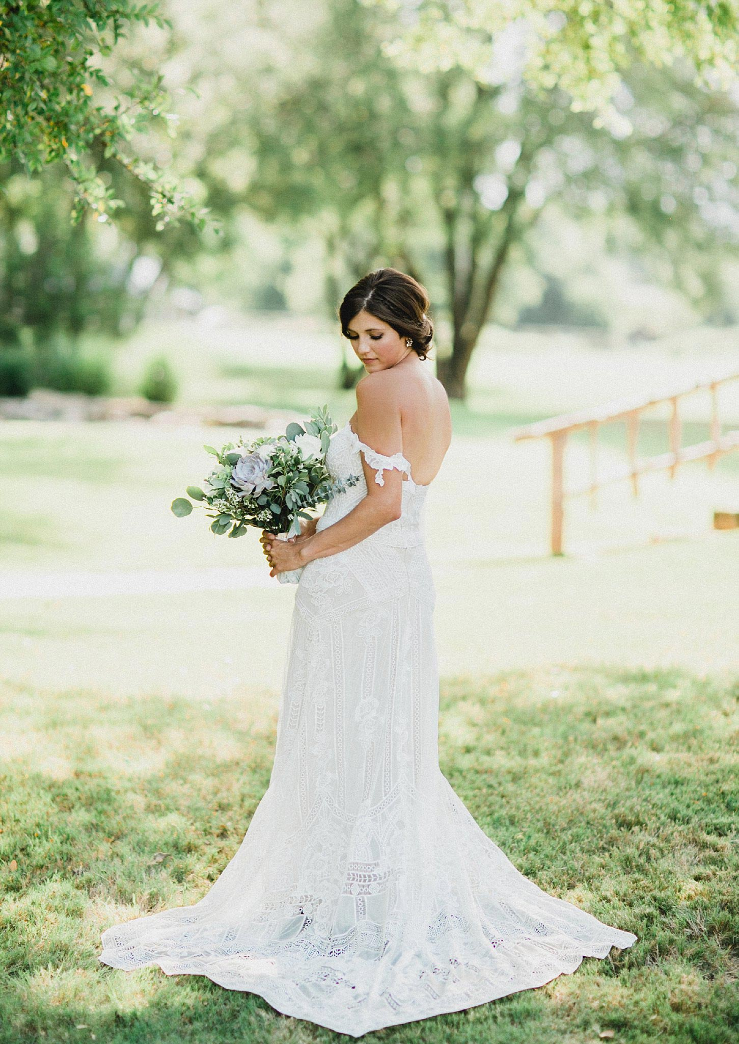 Bride in boho lace dress holding a light greenery bouquet