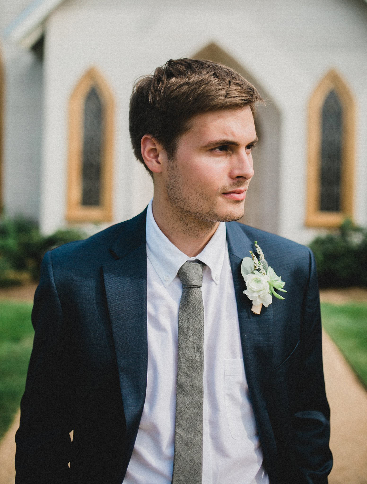 Groom in navy suite with succulent boutonniere