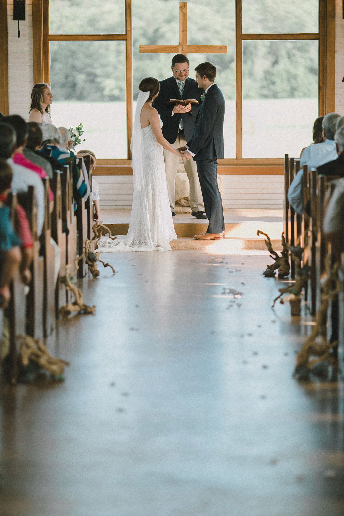 Brooks at Weatherford wedding ceremony with driftwood lining the wedding aisle