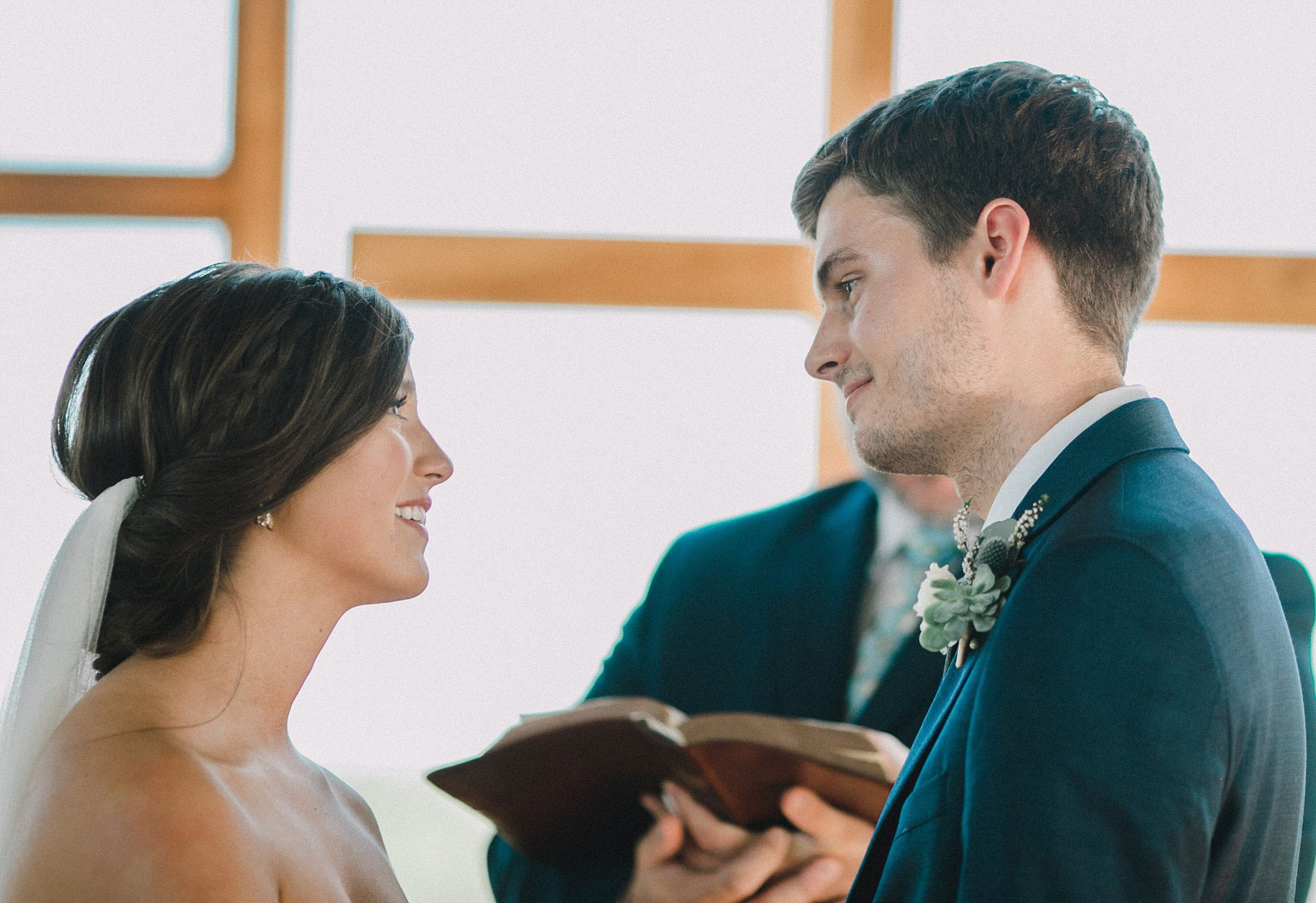 Bride and groom reading scripture during ceremony