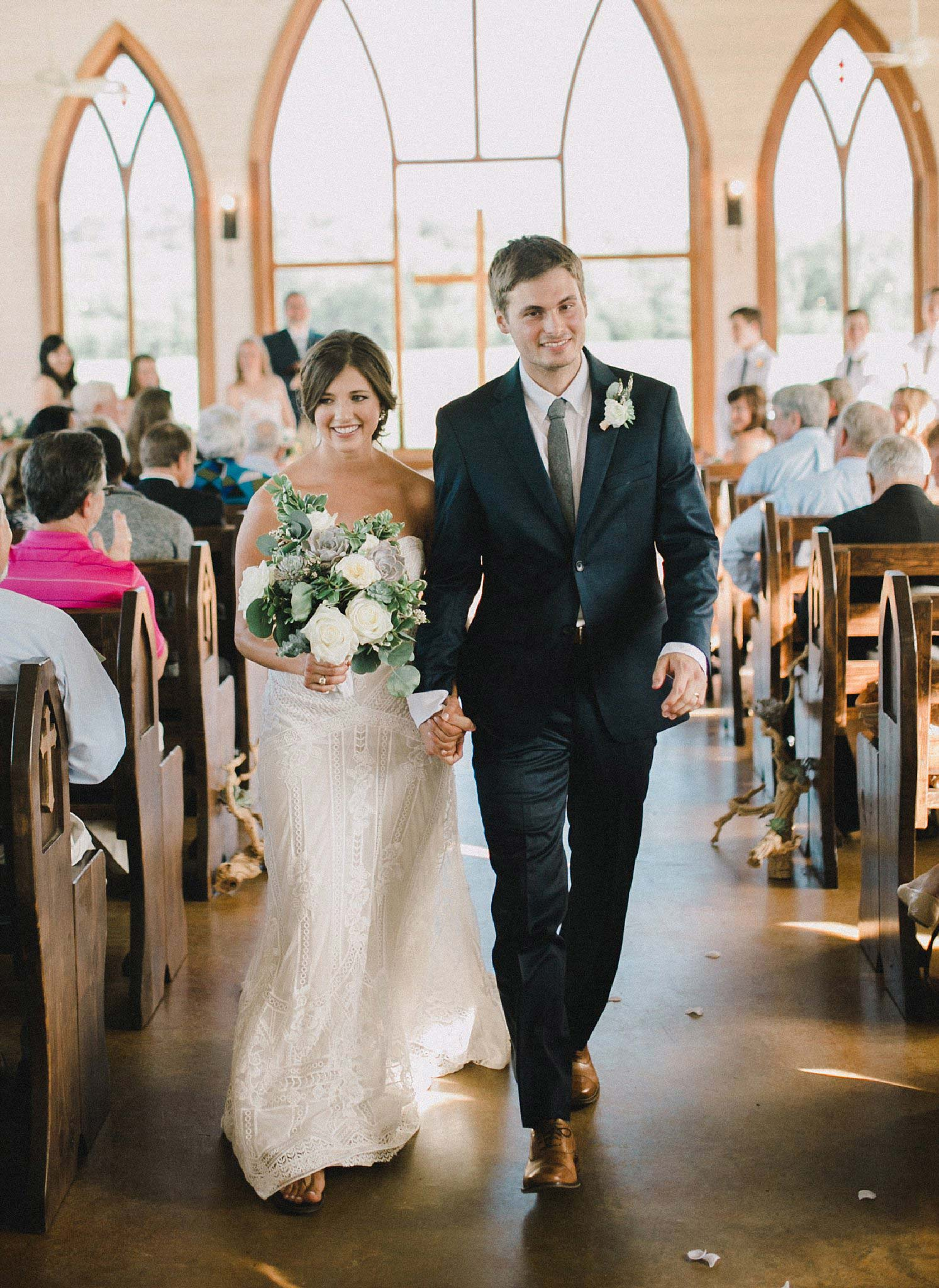 Bride and groom exiting the Brooks at Weatherford white chapel