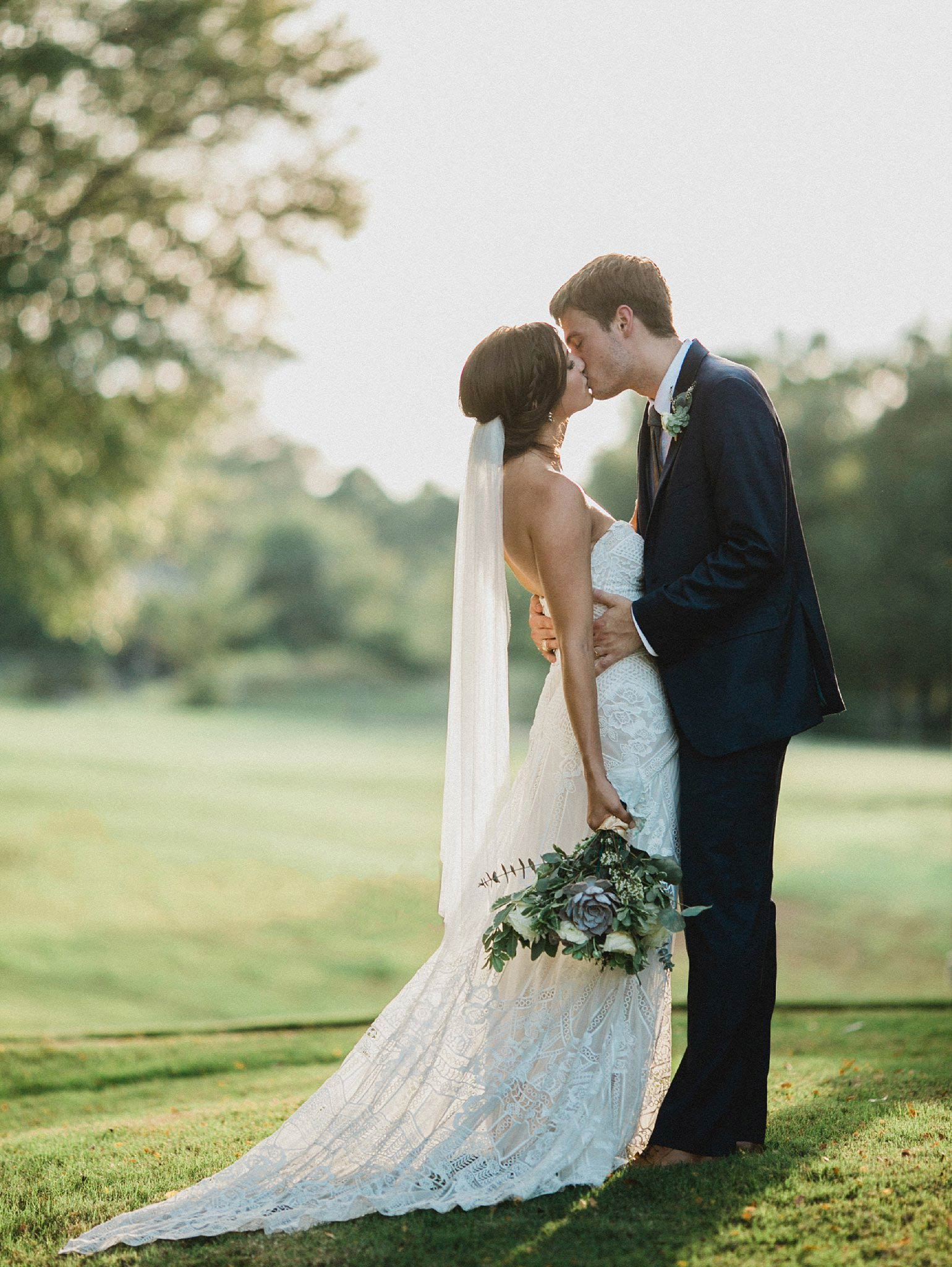 Bride wearing a lace boho dress kissing the groom while holding a greenery and succulent bouquet