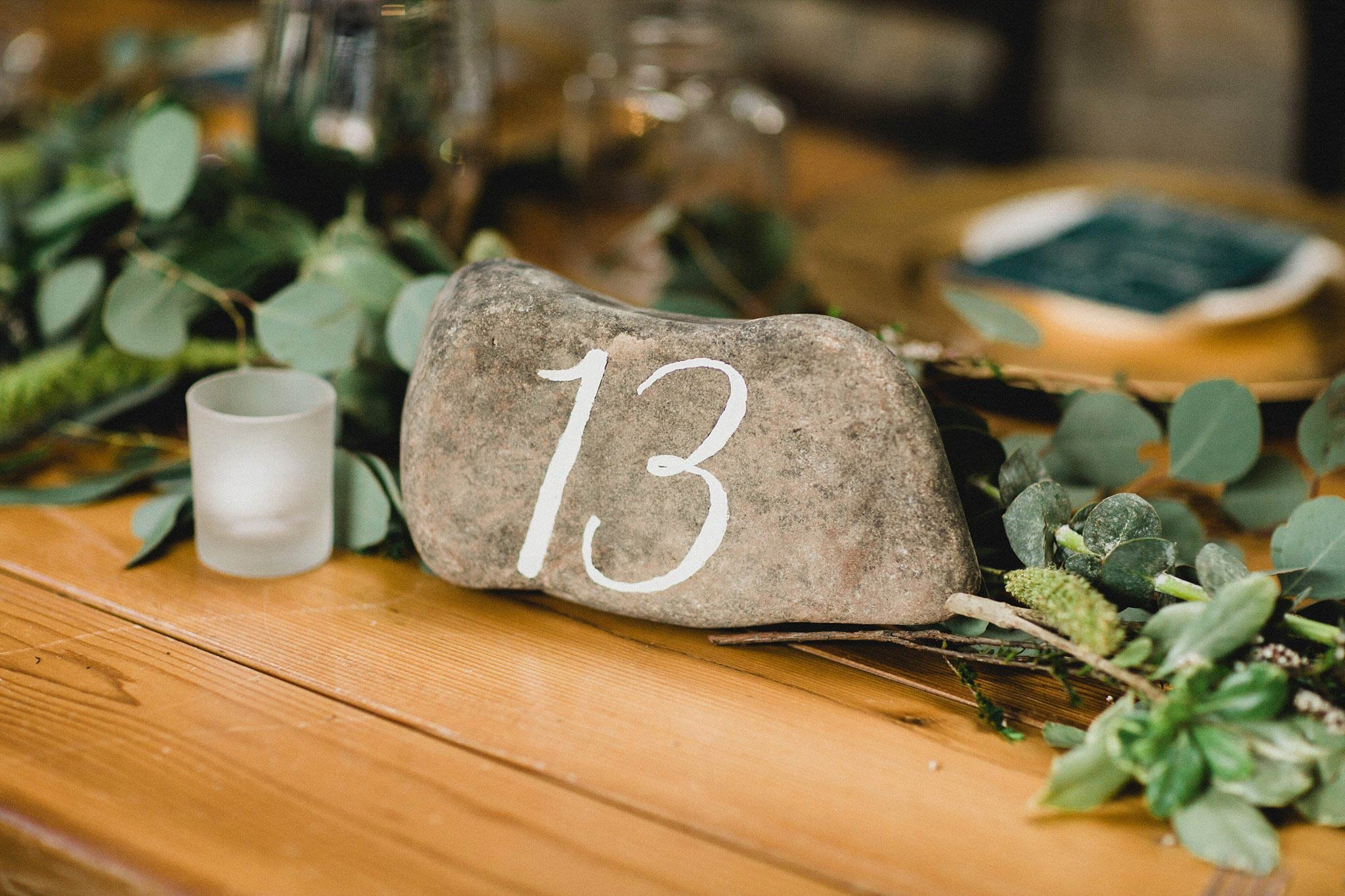 Rock table number with white calligraphy for organic mountain wedding