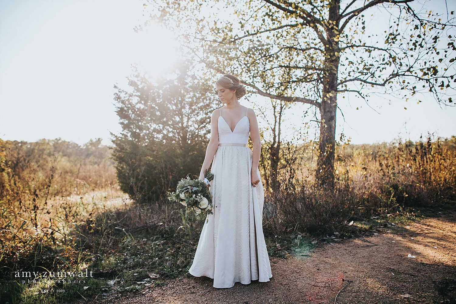 Bride holding a greenery bouquet in woodland scenery