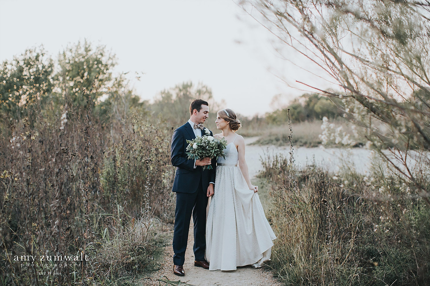 Bride and groom at Trinity River Audubon Center in the fall with tall brown grass