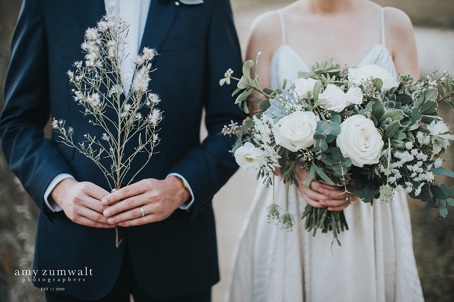 Bride and groom holding greenery
