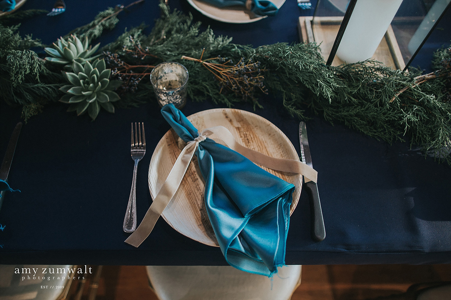 Wood plate with a light blue napkin tied with velvet ribbon