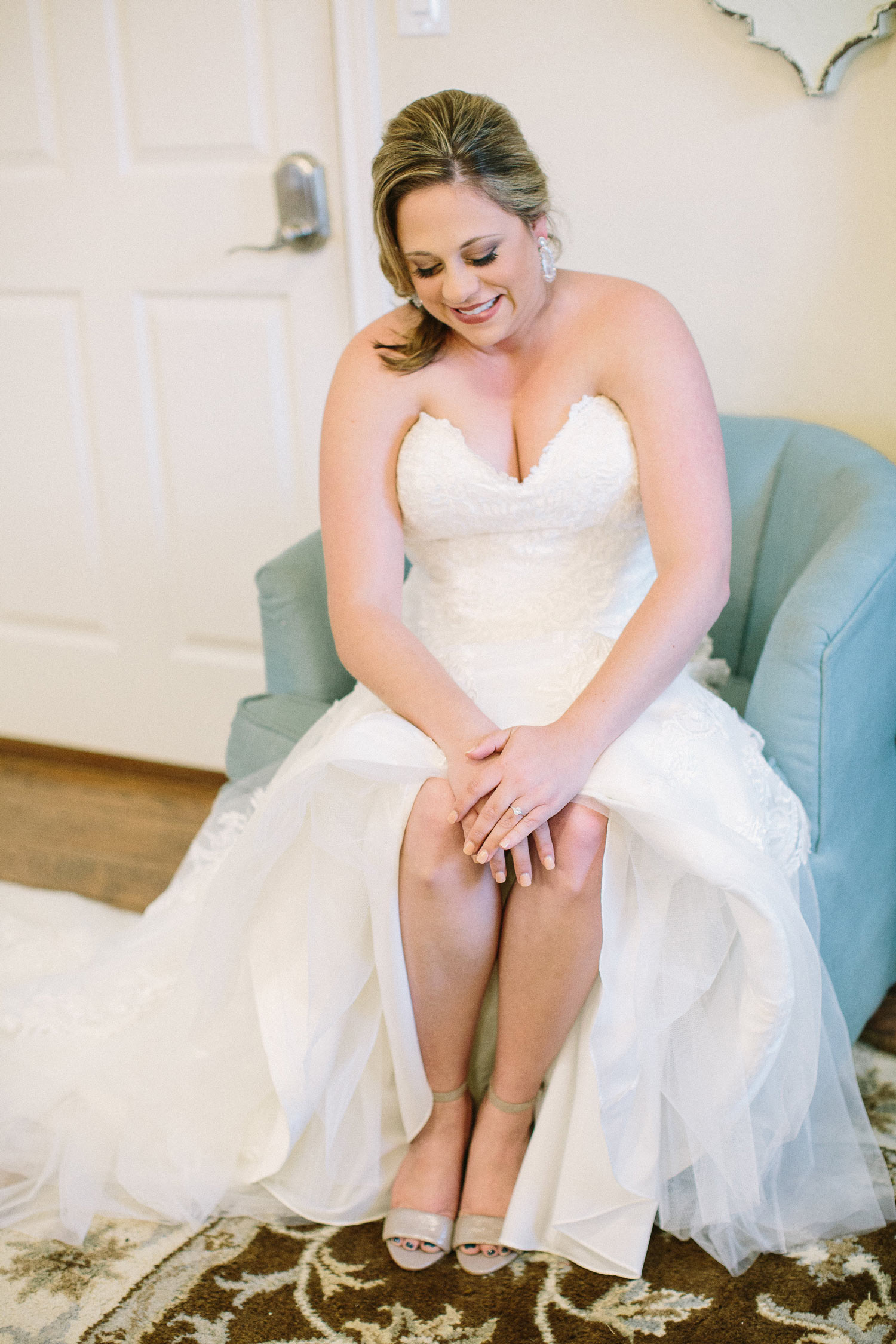 Bride sitting in blue chair at the Orchard in Azle bridal suite