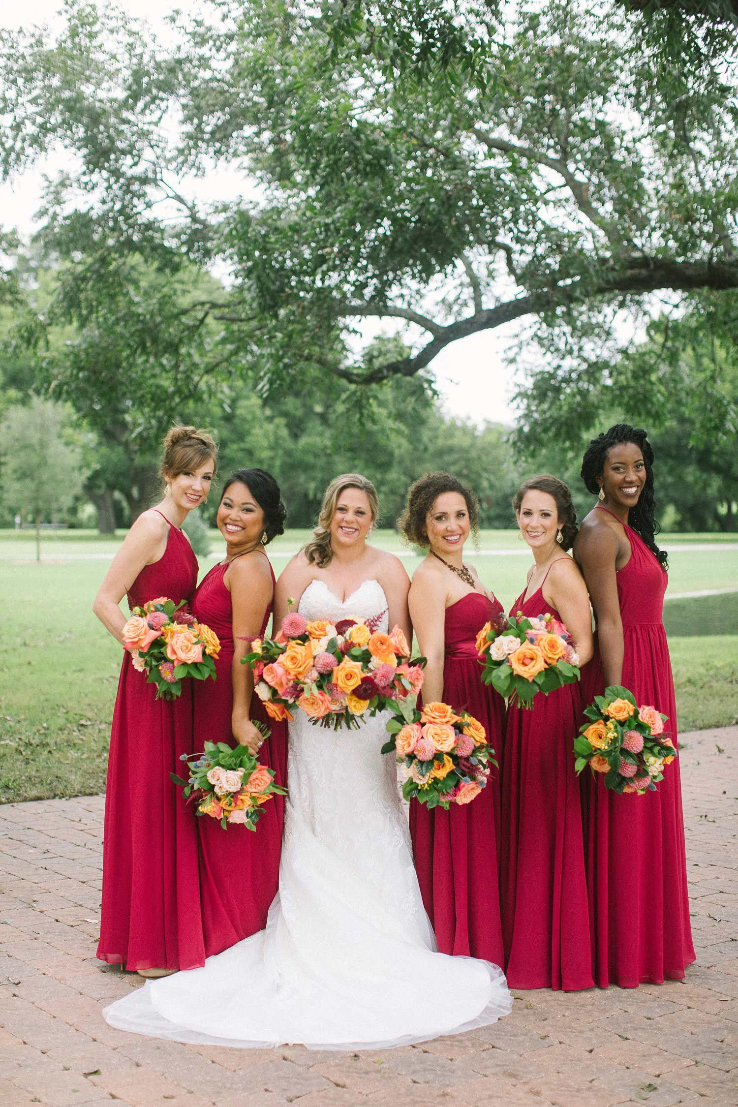Bridesmaids with burgundy dresses and colorful flowers at the Orchard in Azle