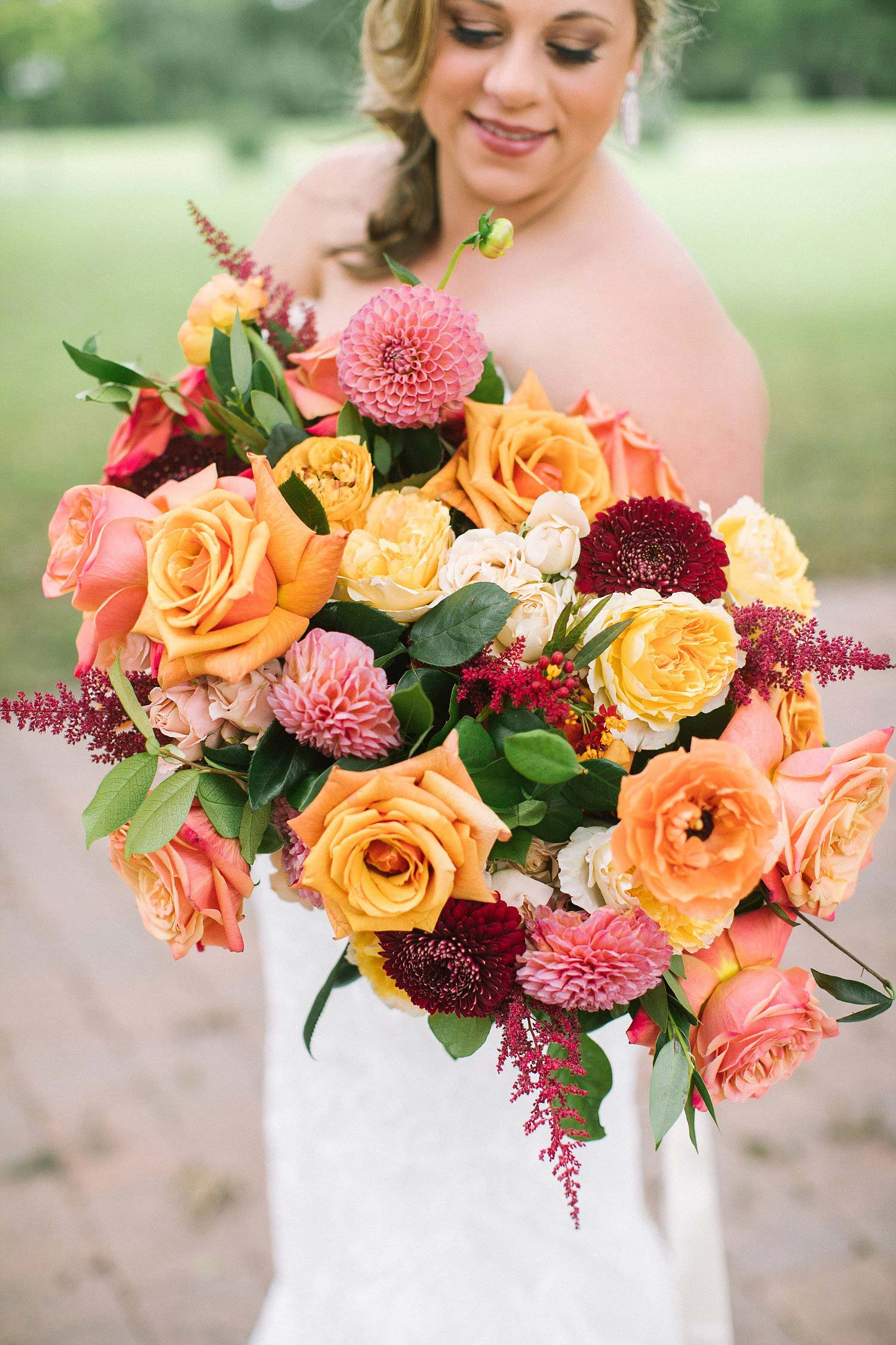 Bride holding apricot coral yellow and burgundy bridal bouquet