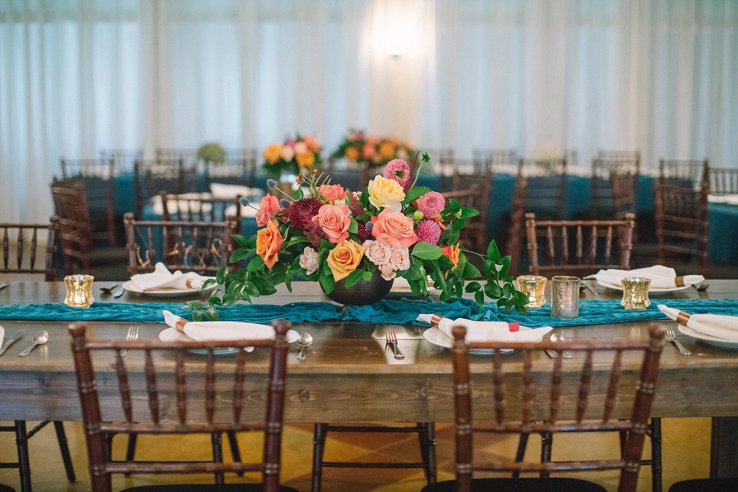 Farm table with a teal runner and colorful fall flowers