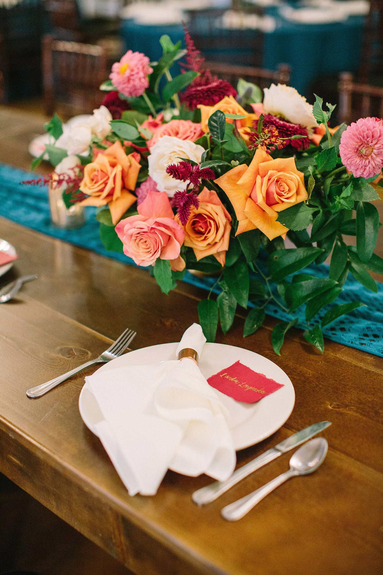 Napkin with copper napkin ring on white plate with a red escort card