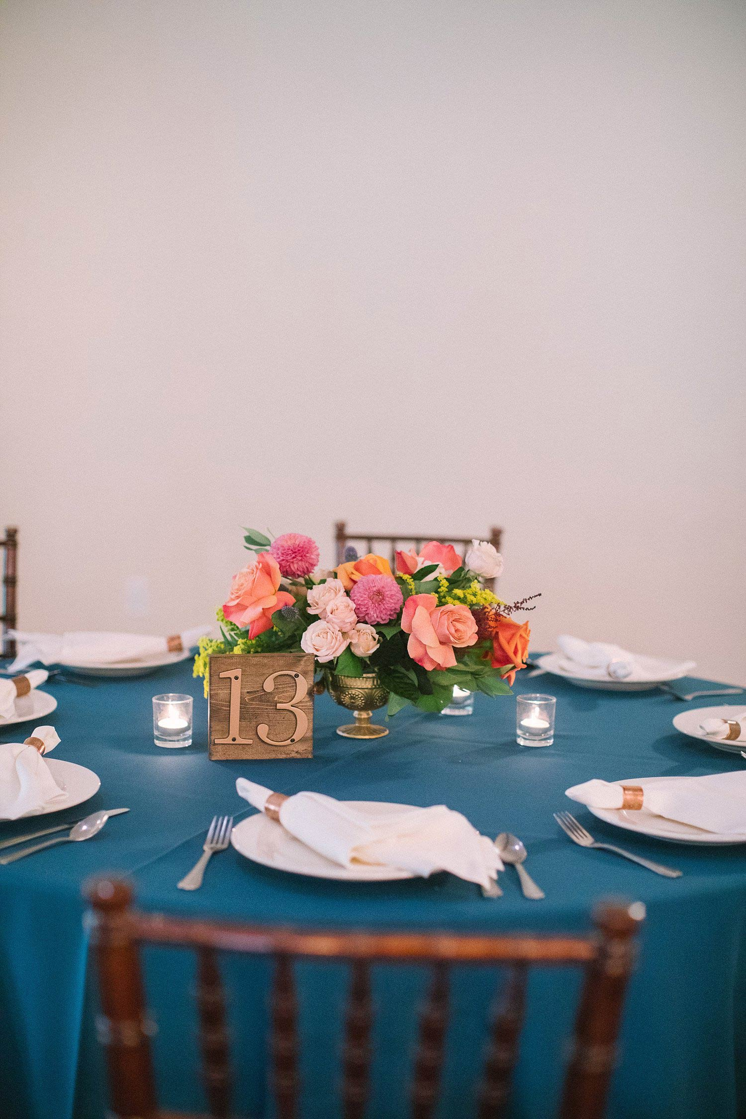 Colorful flower centerpiece with a wood table number
