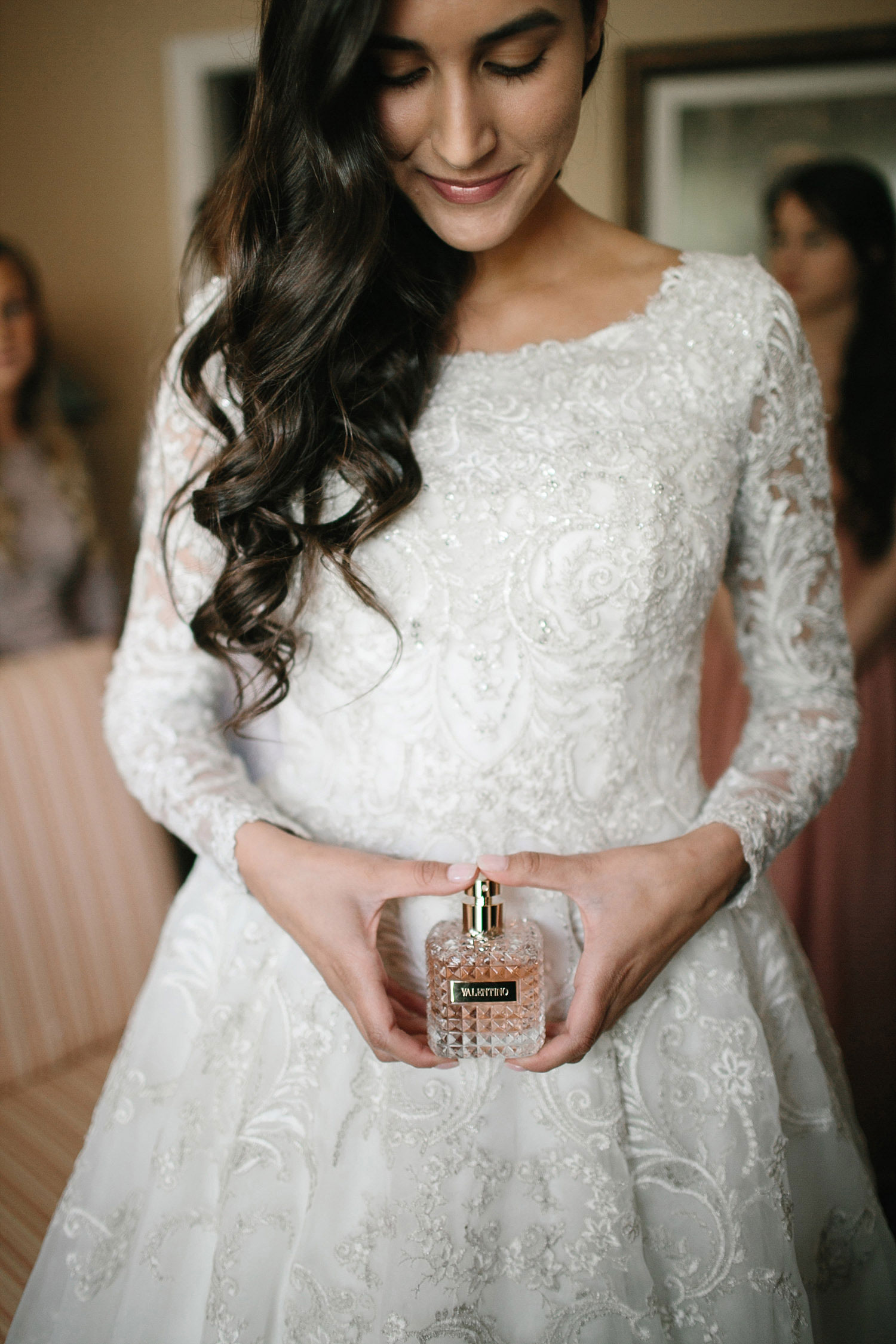 Bride in long sleeve lace dress holding a perfume bottle