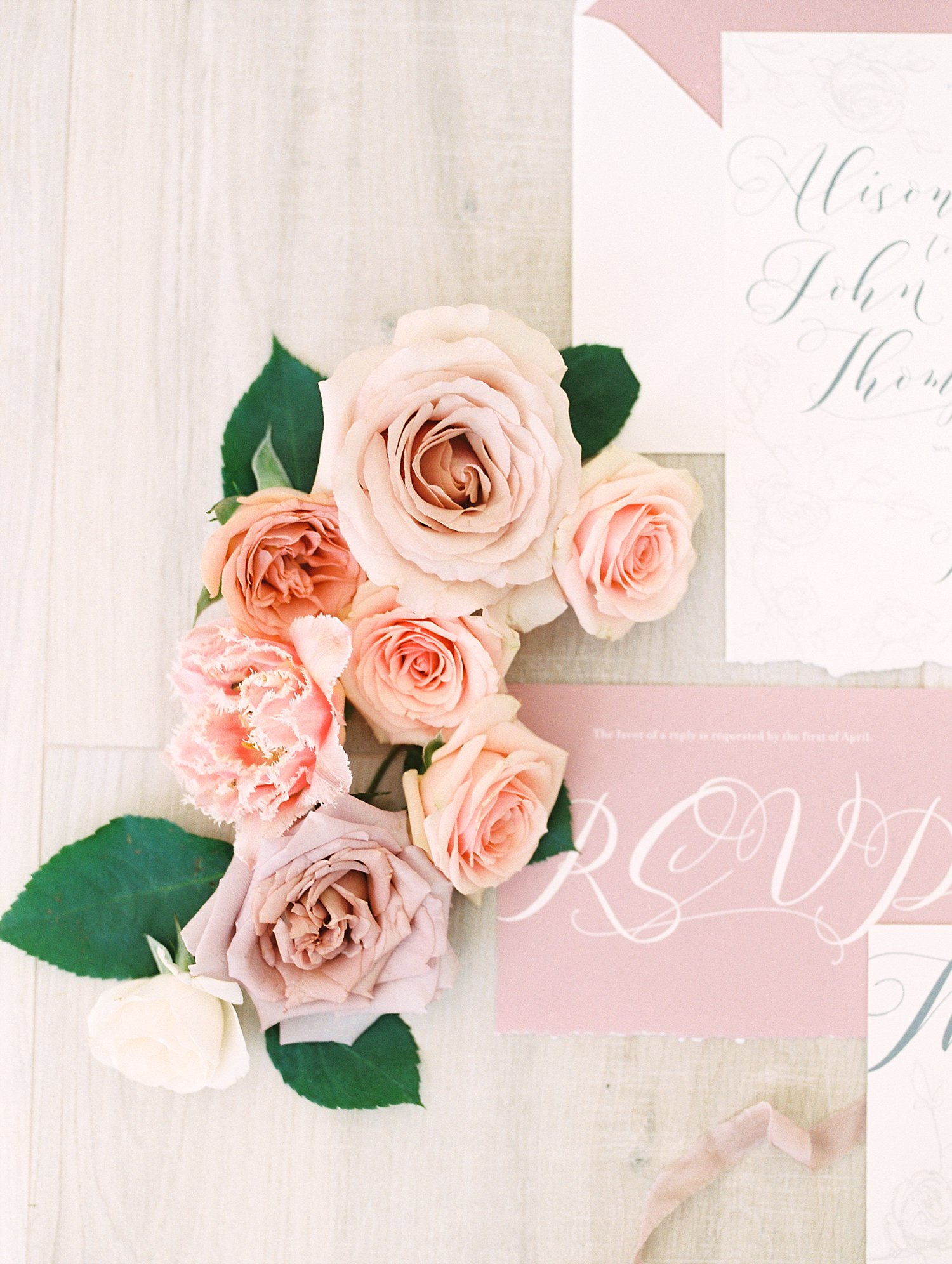 Roses next to a pink RSVP card