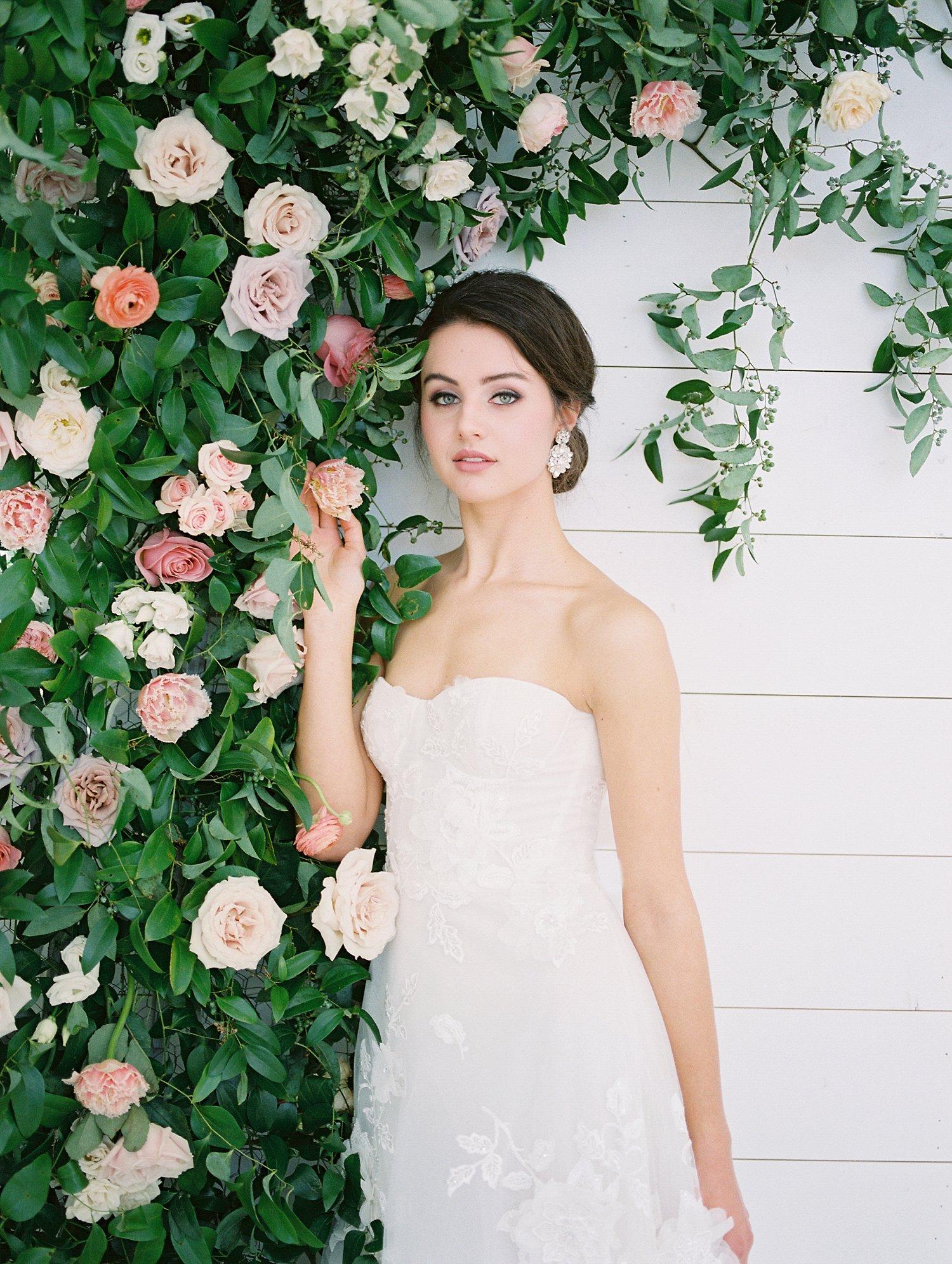 Bride standing next to a rose bush