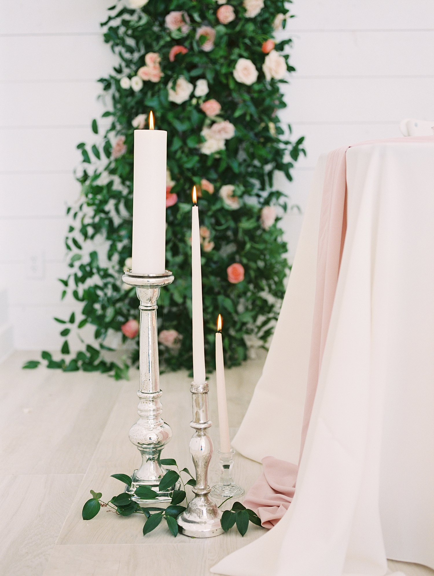 white tapered candles with silver candle sticks
