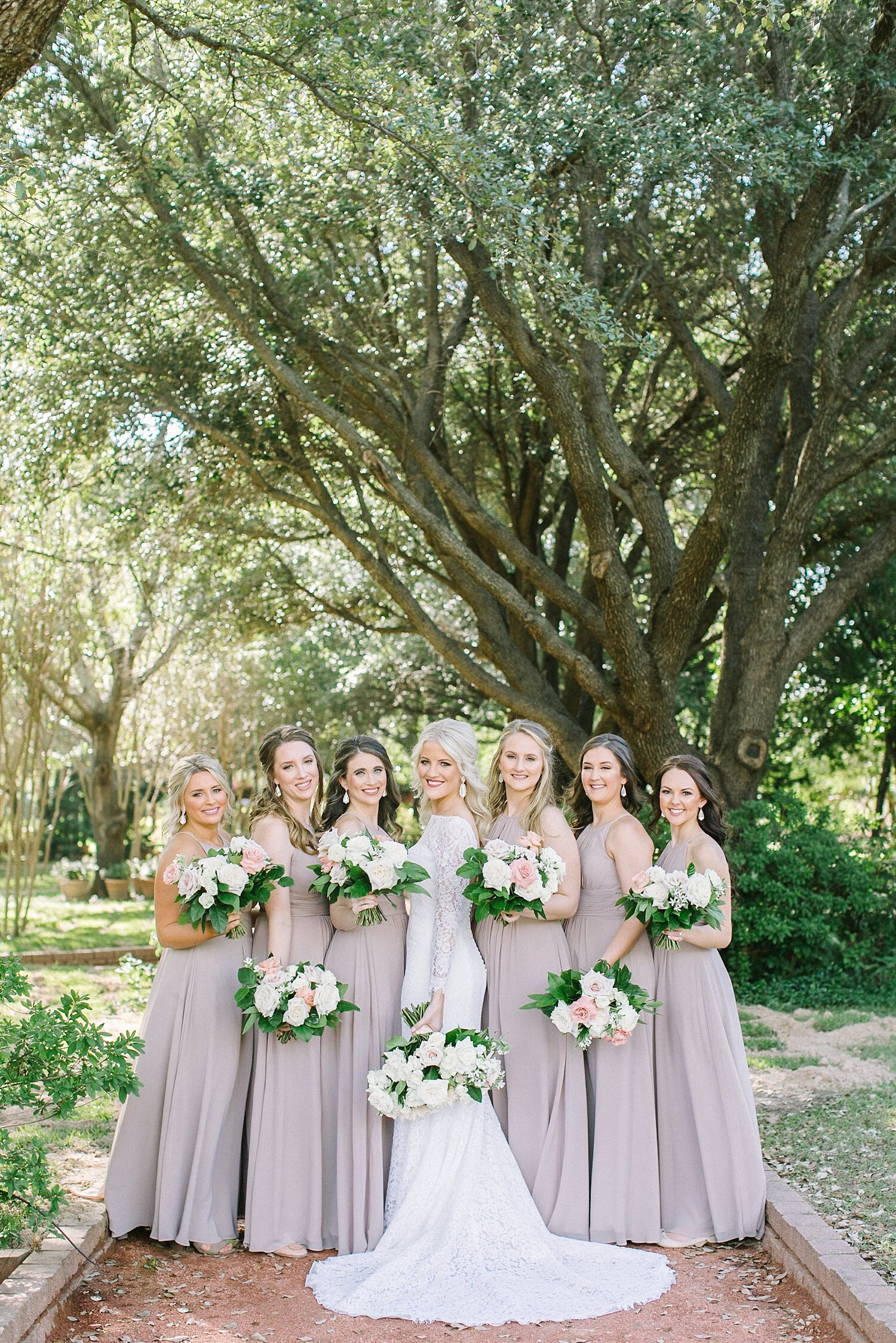Bride and her bridesmaids in taupe dresses with white bouquets