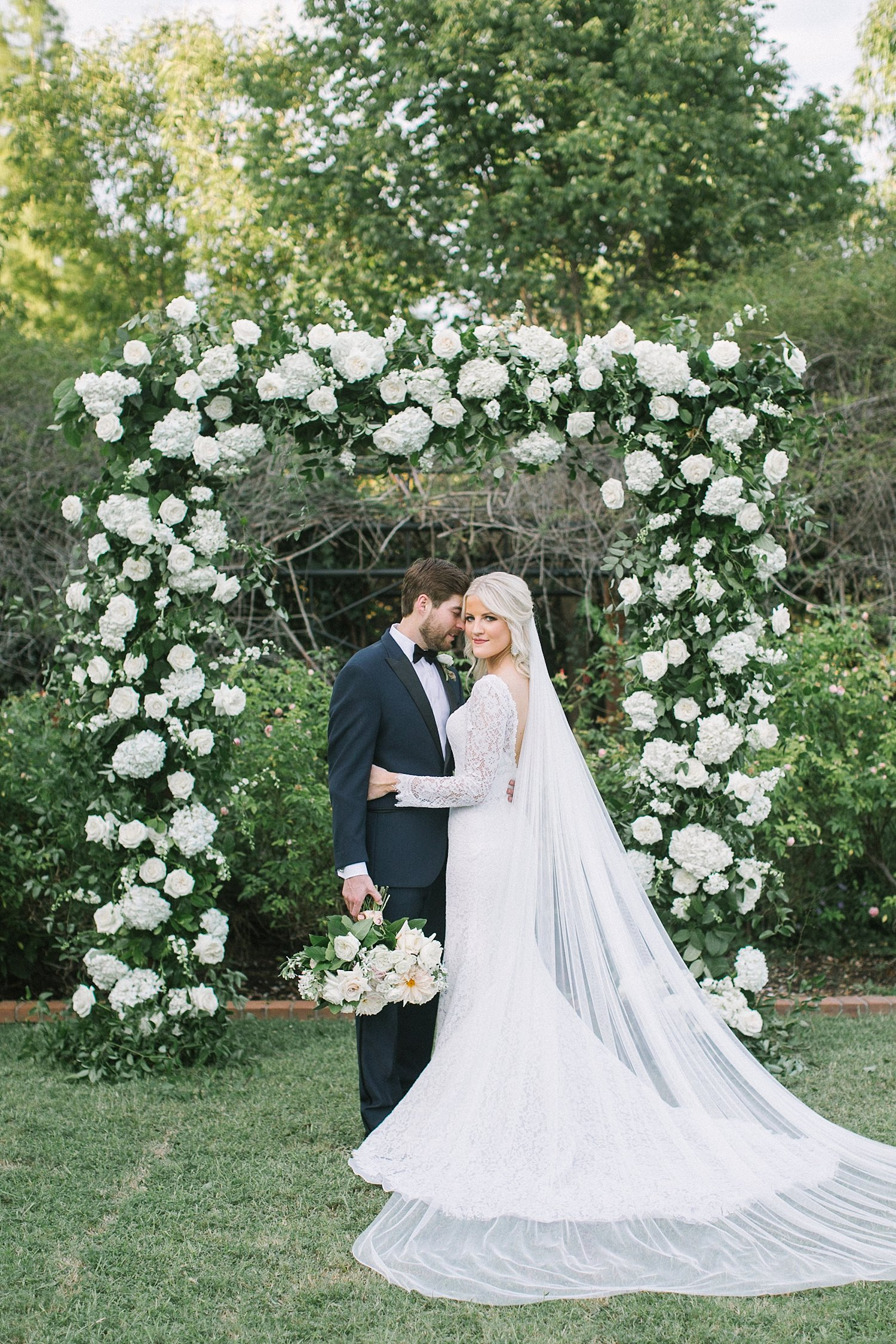 Bride and groom in front of white organic archway at clark gardens wedding