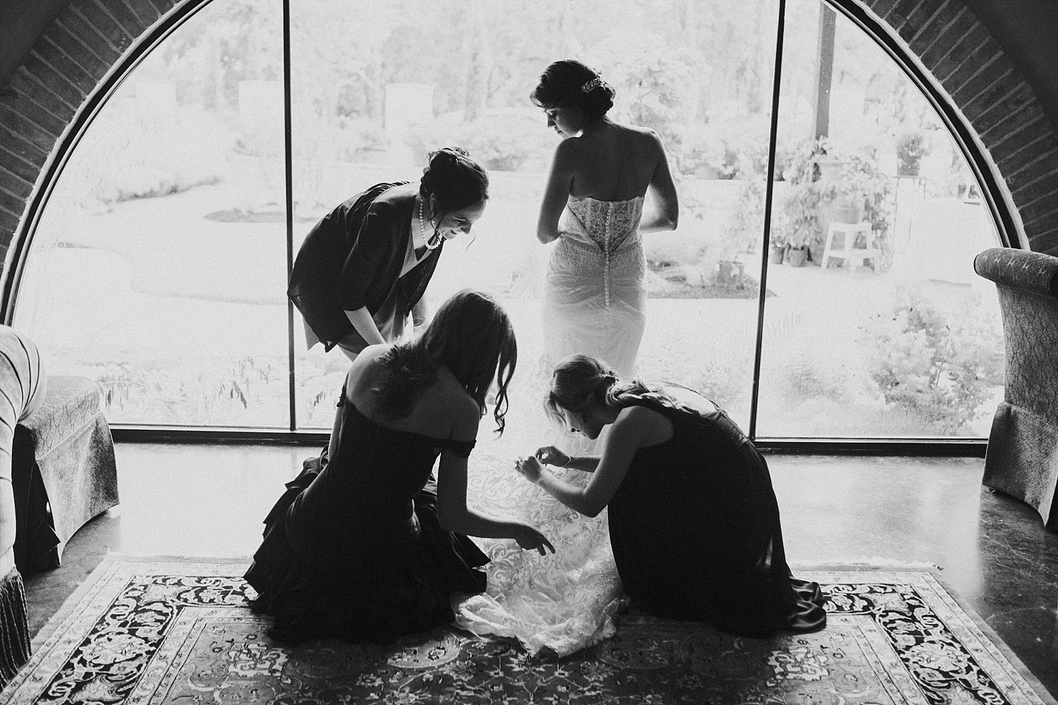bridesmaids putting on the brides dress in a black and white photo