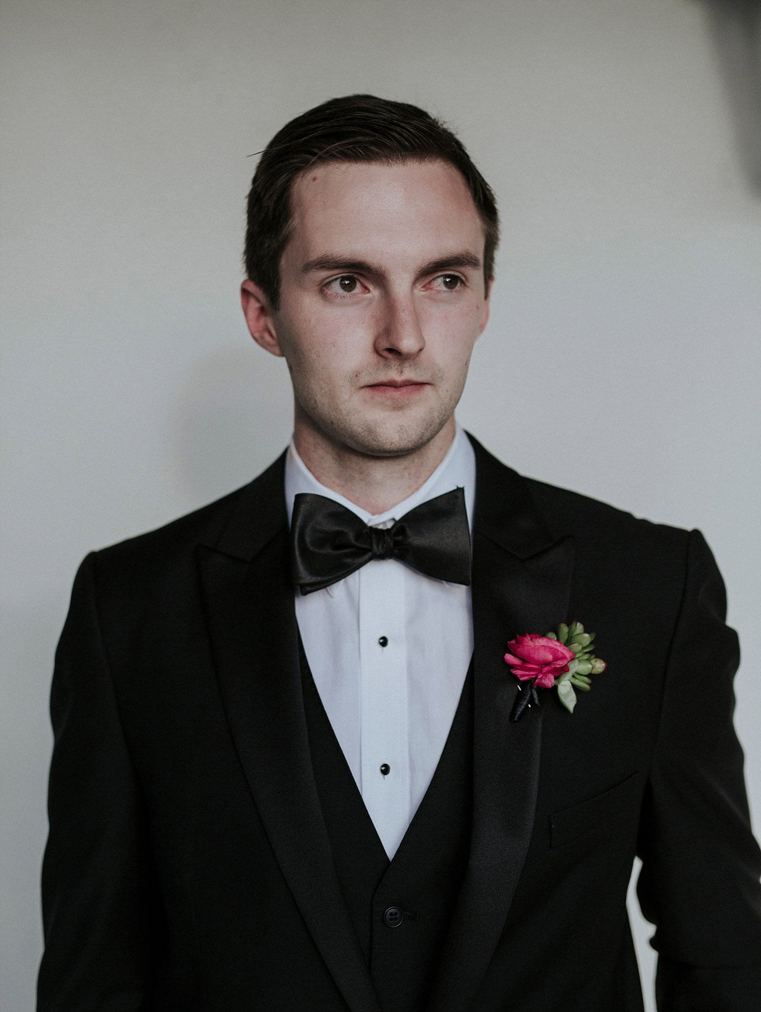 Groom wearing a black tux and pink boutonniere