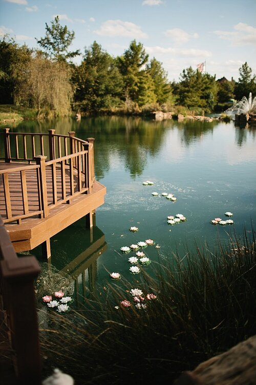 Floating lillies and candles in water at a wedding ceremony