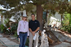 Mark Abbott and Anastasia Studer from the Riverside County Department of Environmental Health stand outside of a resident's home before collecting a sample from their new water treatment system