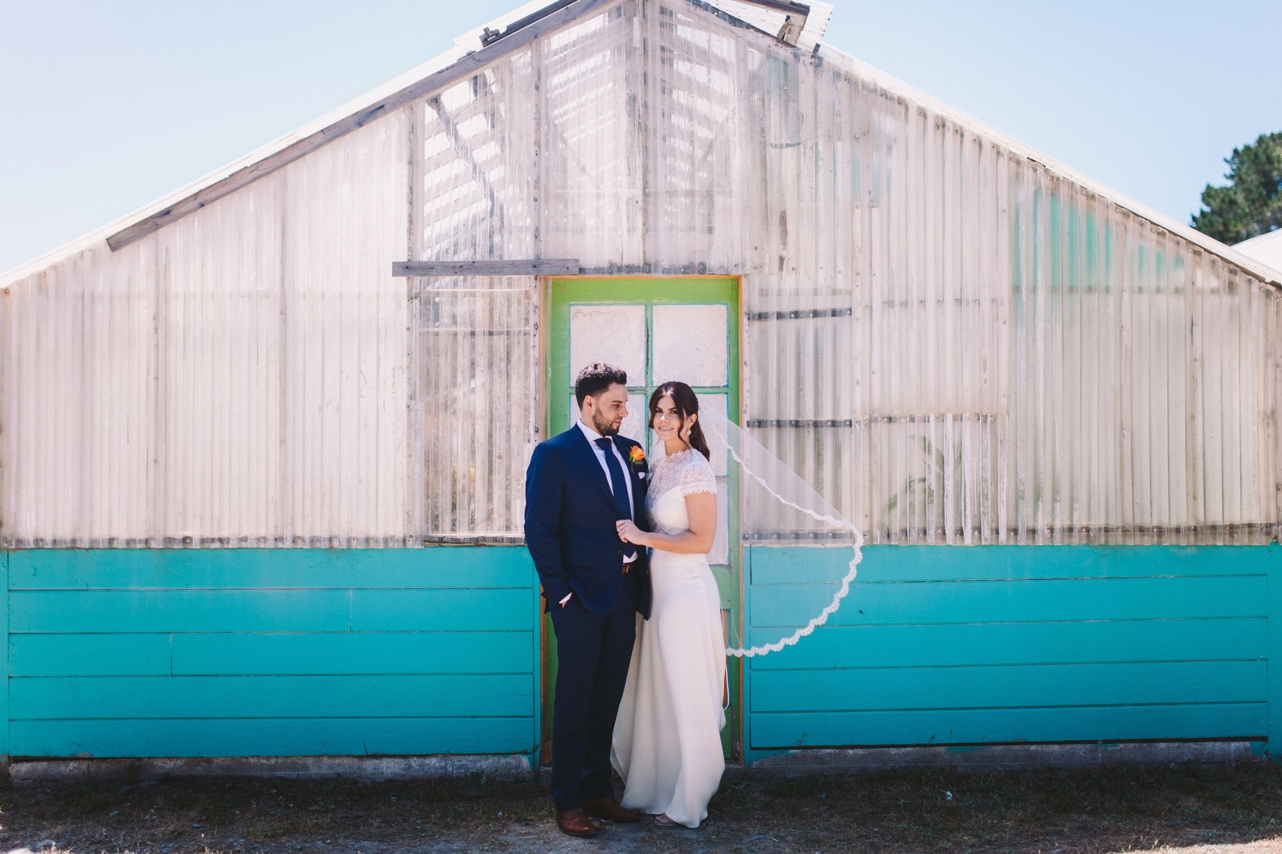 Bride & Groom Portrait in front of Brightly Painted Greenhouse at Shelldance Orchid Gardens