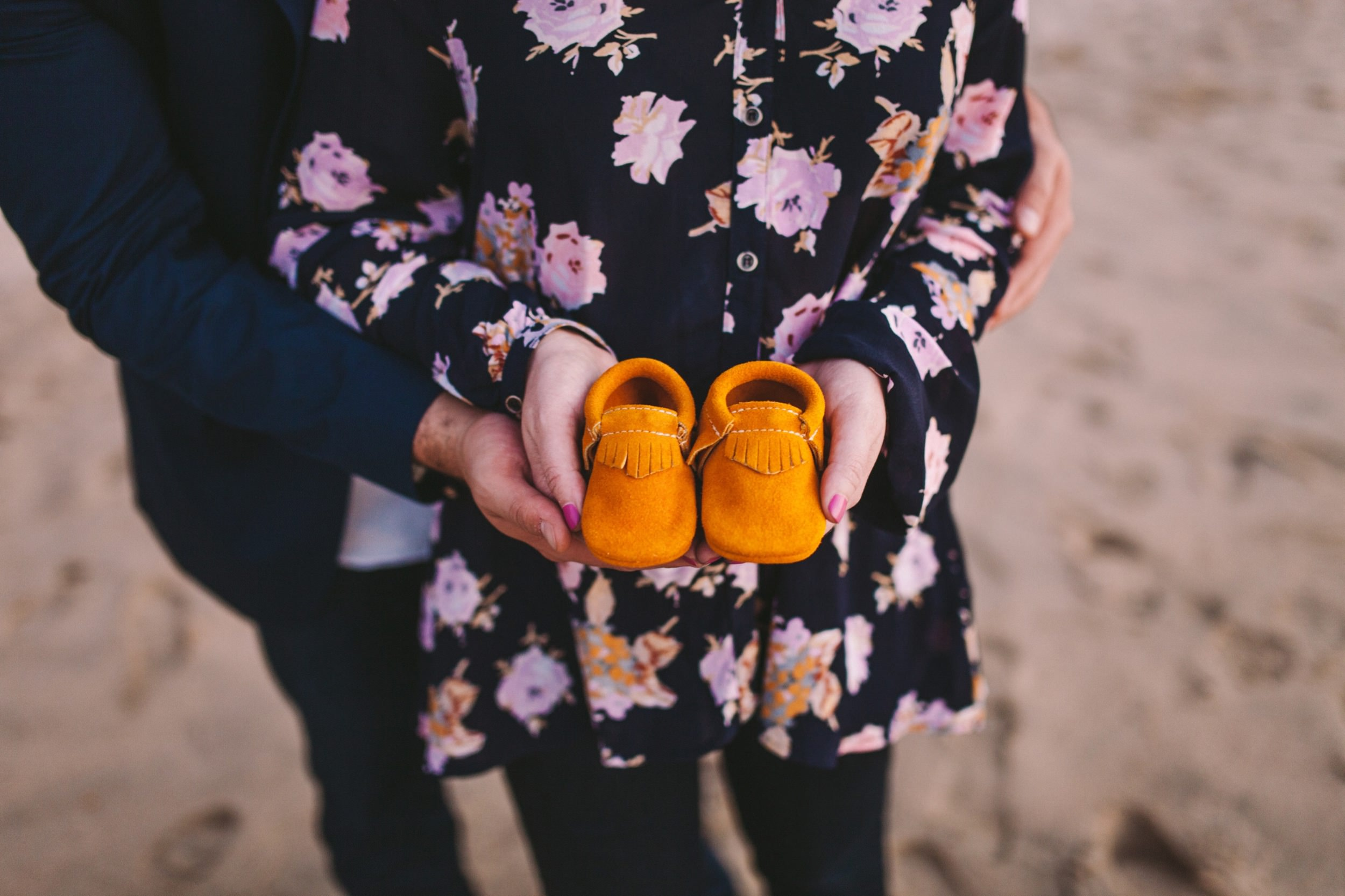 Pregnancy Announcement Holding Yellow Baby Suede Moccasins
