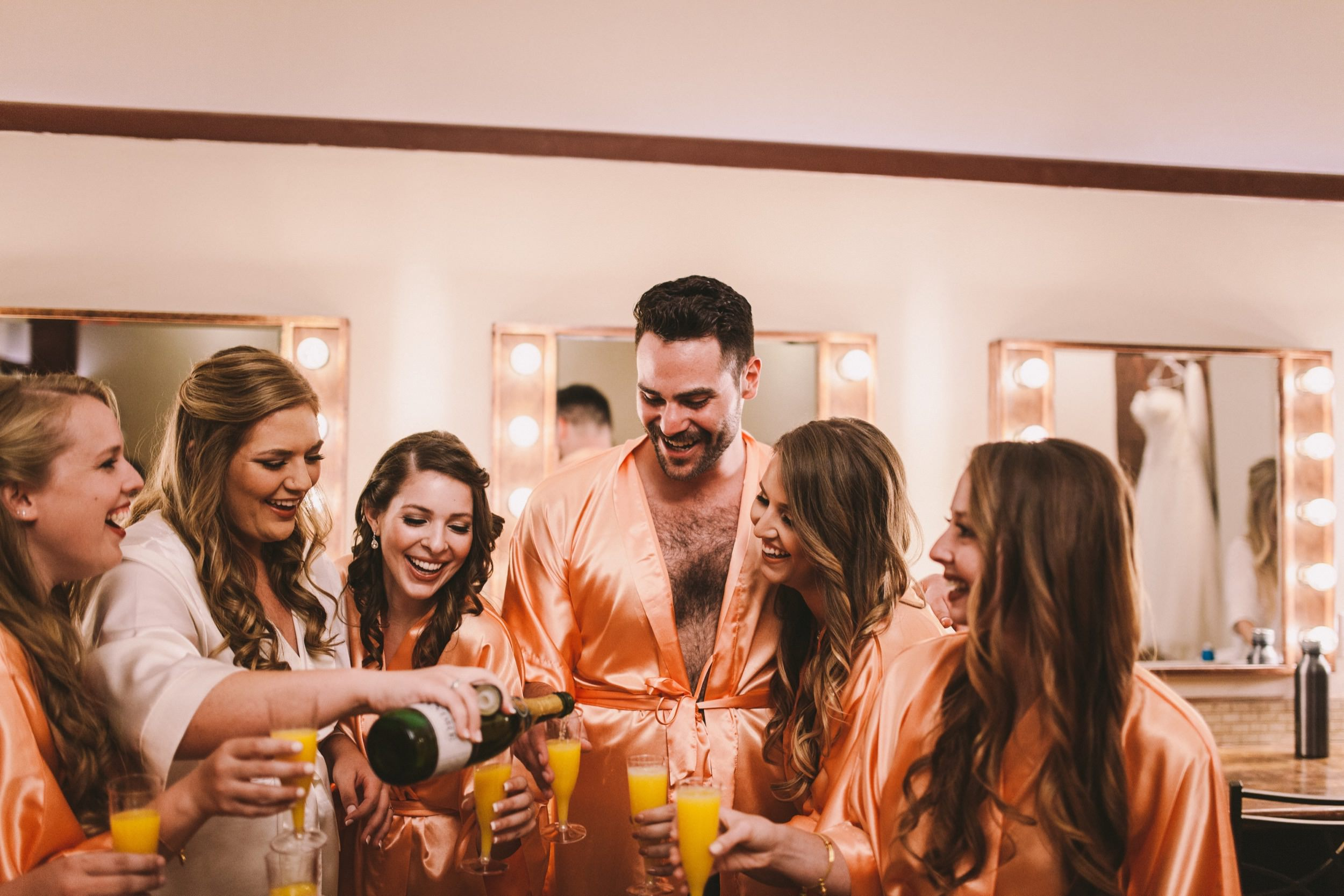 Bride Pouring Mimosas Morning of Wedding with Bridesmaids and Bridesman