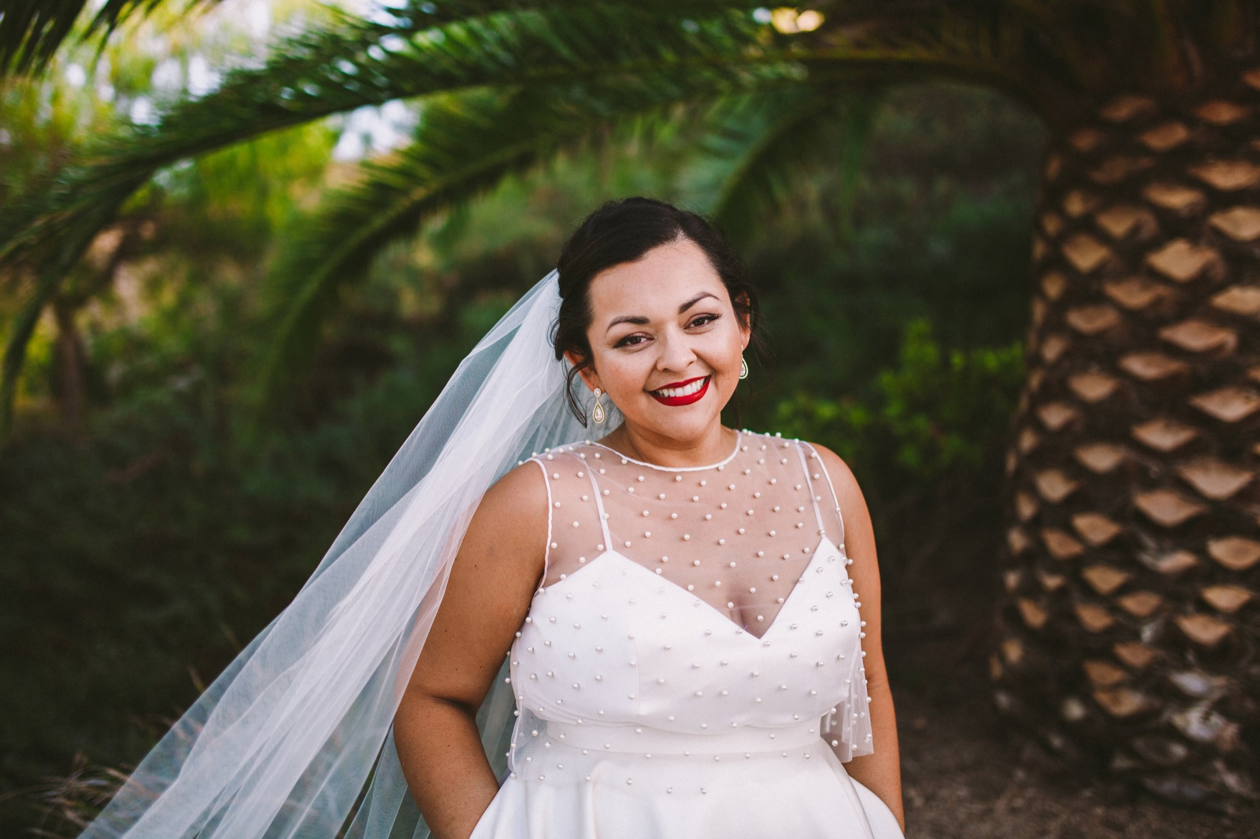 Beautiful Bride with Red Lipstick and BHDLN Separates in front of a Palm Tree