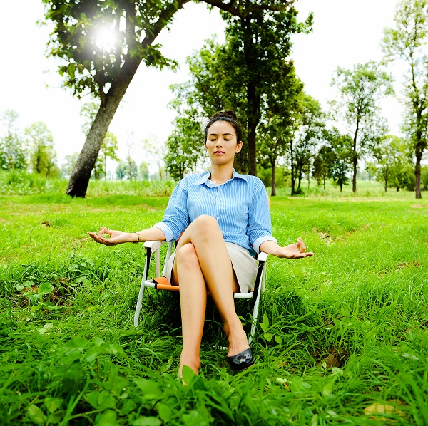 young woman meditating outside on chair field.jpg