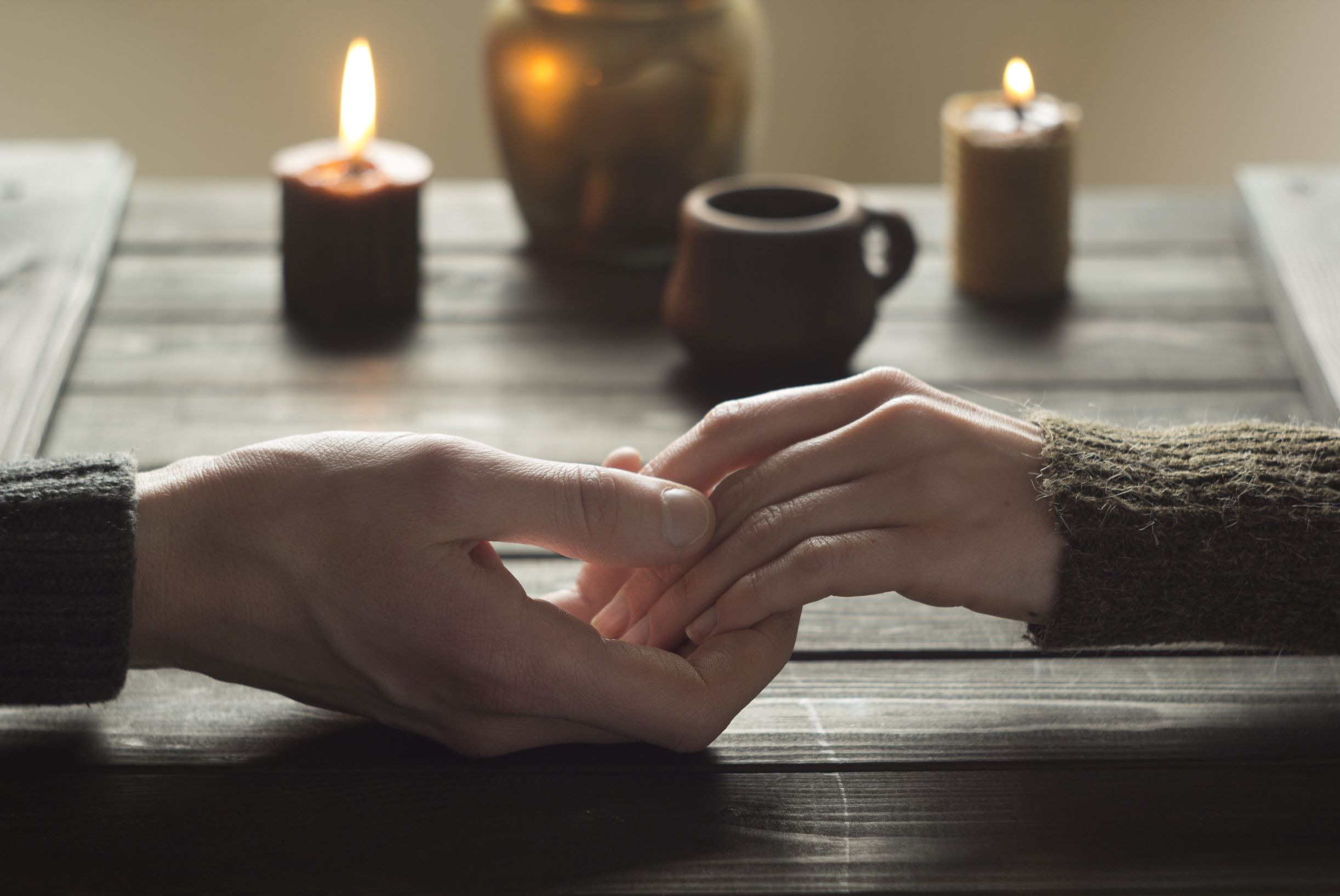 couple holding hands on table with lit candles.jpeg