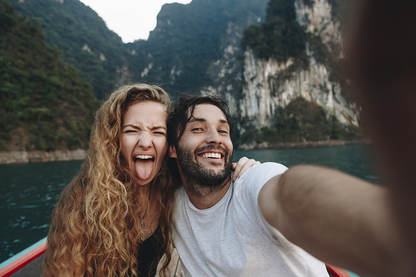 Happy man and woman on a boat in on a mountain lake.jpg