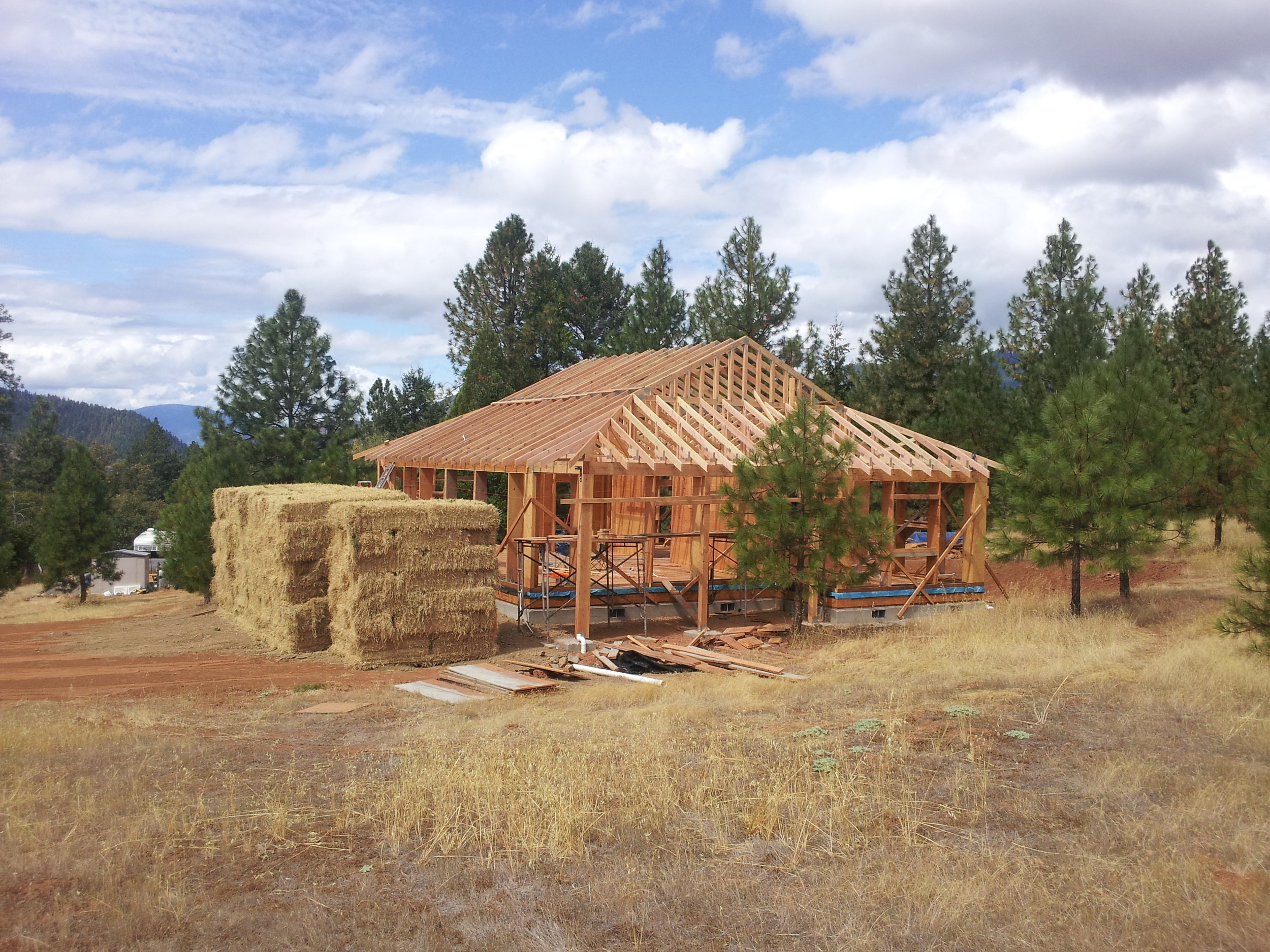 "I-Joist or LVL type of post-and-beam system uses 3-string bales stacked on edge (15"" wide) for maximum insulation value per inch of wall thickness.  Uses straw bale shear wall and interior partition shear walls."