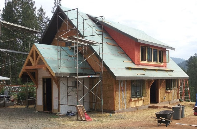 Passive solar straw bale house using prefabricated steel brace frames for shear.
