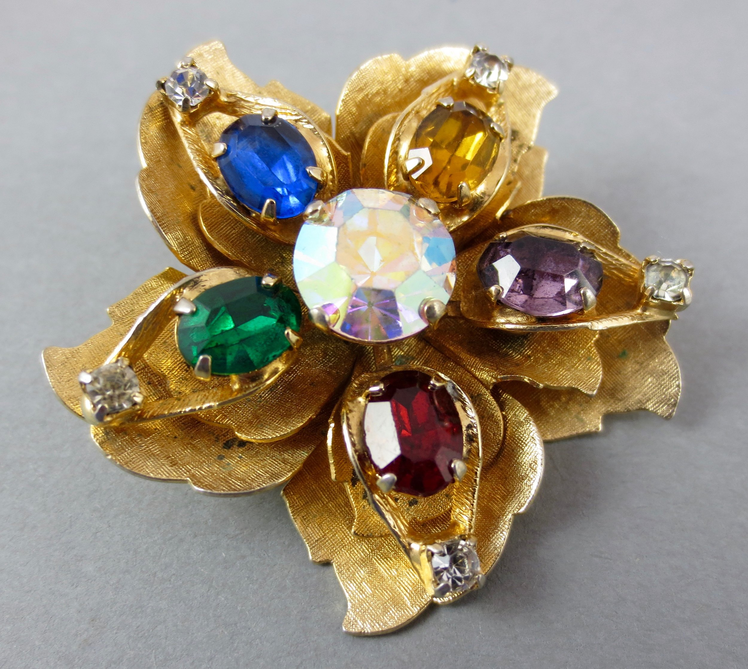 gorgeous vintage WARNER flower brooch. layered gold metal leaves, adorned with multi colored rhinestones. resparkable vintage.