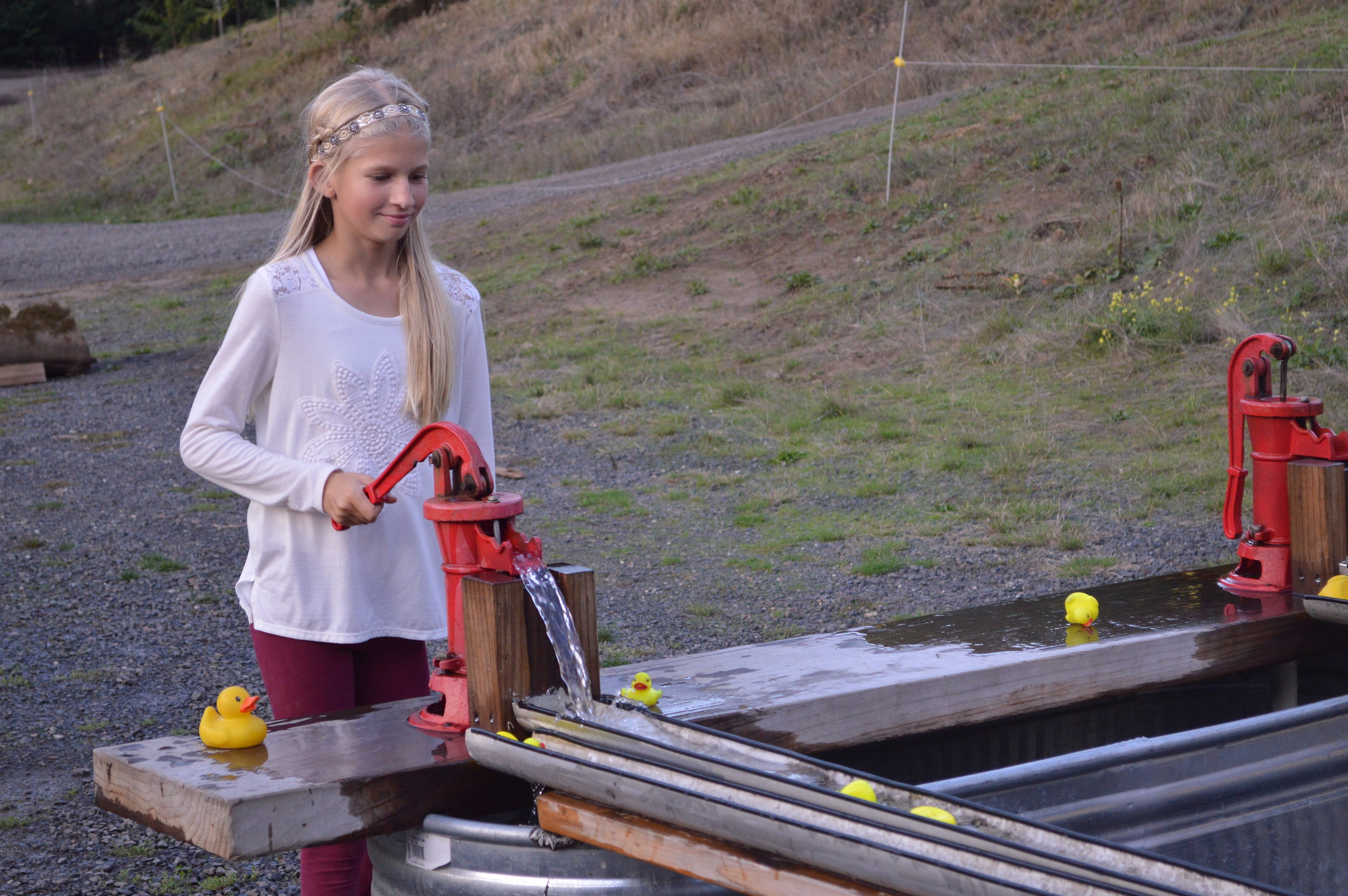 Brynne Hathorn races rubber duckies along the pipe by using a water pump system of the Mahaffey's own invention.