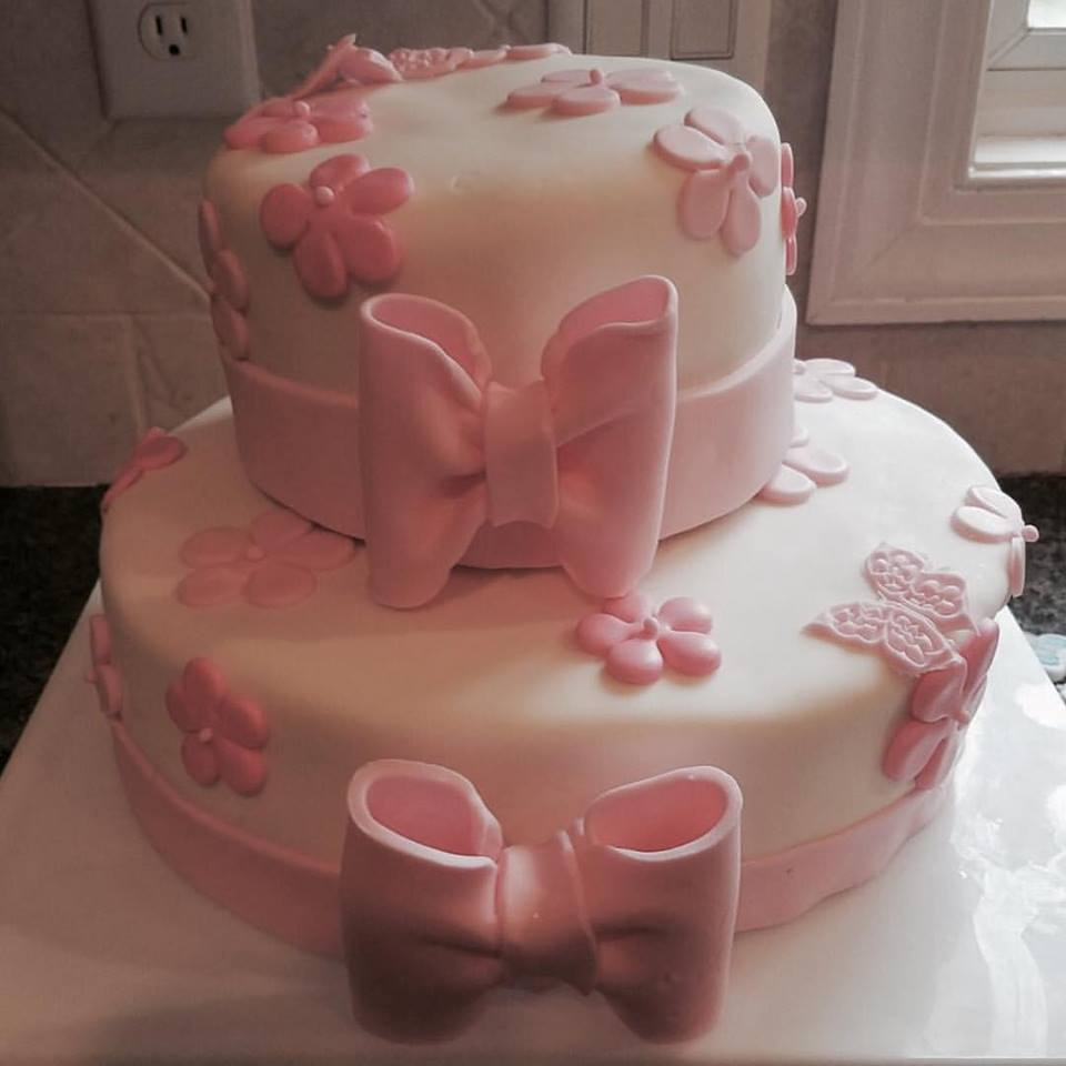 Elegant fondant cake with pink flowers and giant pink ribbons